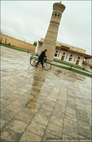 Homme et son vélo, passantdevant un petit minaret